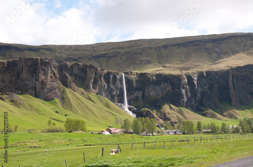 Waterfall and small farm in remote Iceland Poster