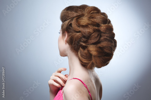 Beauty portrait of a girl with a voluminous hairdo from the back against a gray background. © ksi