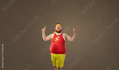 Fat funny freak man in sports clothes points with his finger up.