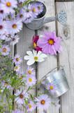 fleurs bleues et mauves et pot en métal sur table bois