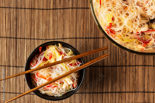 Glass noodles salad and chopsticks, in a black plate Poster