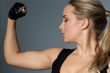 close up of woman posing and showing biceps in gym - 172884826