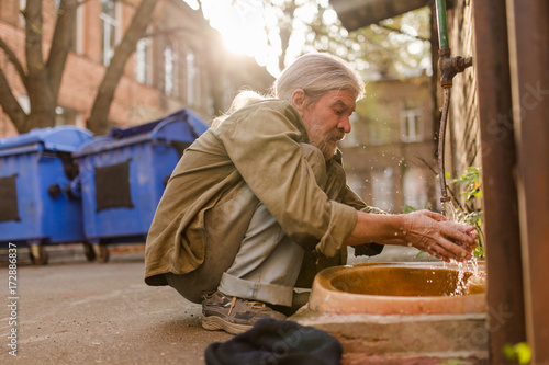 Squating old tramp cleaning face under water. Street hygiene, homeless man washing face.