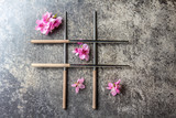 Chopsticks and sakura flowers on gray stone background. Japanese food concept. Top view, copy space