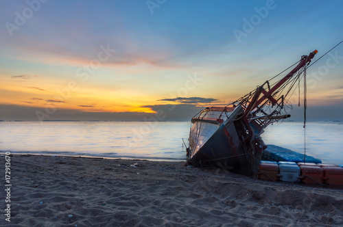 Spoed canvasdoek 2cm dik Schipbreuk An old shipwreck or abandoned shipwreck, Boat capsized on the sand beach in beautiful colorful twilight sunset background with plastic tank movement