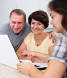 Daughter learning  parents searching documents on laptop - 172927437