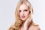 Portrait einer hübschen jungen Frau mit langen blonden Haaren vor weissem Hintergrund