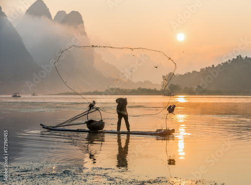 Fotobehang Guilin Cormorant fisherman throws a net with ancient traditional chinese bamboo boats at sunrise - Xingping, China