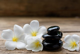 Pile of black zen stones and Frangipani flower on rustic wood background - 172970687
