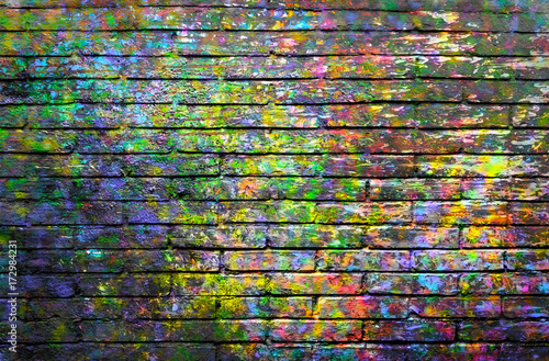 Brick wall painted with spots of paint colors  © Luma
