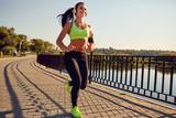 A sports girl in headphones runs through the park. Healthy lifestyle. - 172994835