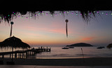 relax with beautiful sunset in the evening bridge chair beach bar beach umbrella boat silhouette at Koh Mak Trad Thailand
