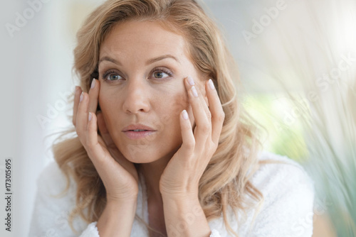 Foto Murales Portrait of attractive blond woman applying anti-aging cream