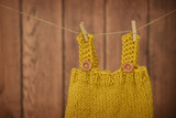 Hand knit baby clothes hanging on a clothesline - 173020427