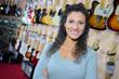 Quadro portrait of female smiling in guitar store