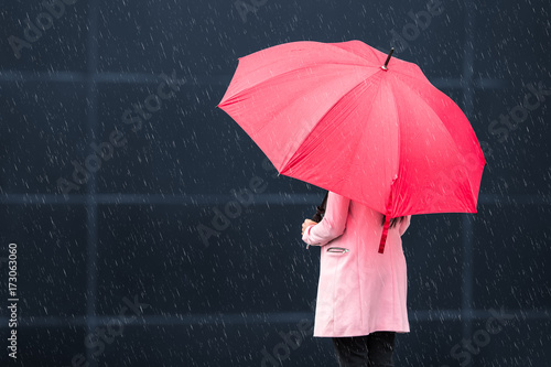 Girl with red umbrella on rainy day