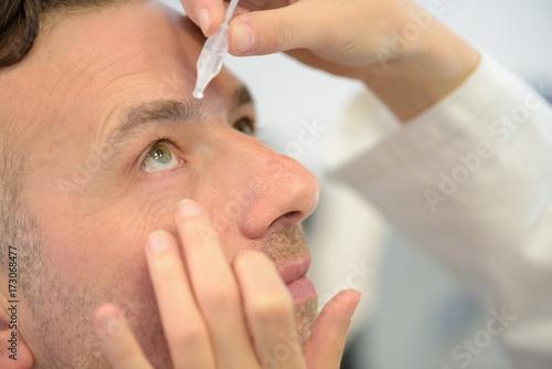 Poster man using eye lotion