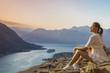 девушка сидит на обрыве скалы с видом на залив и горы в Черногории
