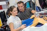 happy young couple shopping clothing in the store