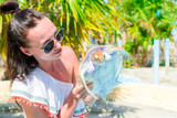 Tourist woman with sea turtle in the hands in exotic reserve - 173111212