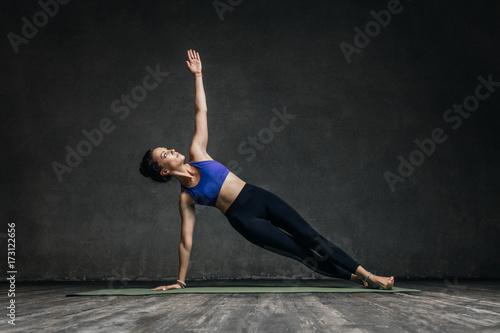 Fototapeta Young beautiful yoga female posing in studio