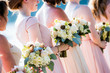 Pink bridesmaids in a row holding bouquet of flowers.