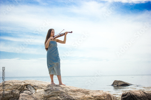 girl in blue playing violin by ocean Poster