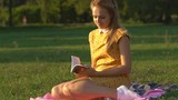 Slow motion. A young blonde girl in a warm sunny day at a picnic. The girl is dressed in a bright yellow dress in flowers. green grass . holds in his hand a book and reads. rest in the park. HD - 173193018