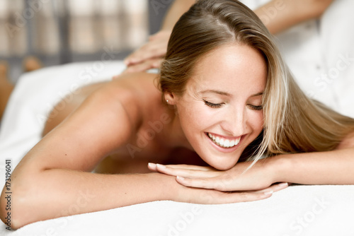 Young blonde woman having massage and smiling in the spa