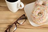 Zwei Donuts, Tasse Kaffee und eine Brille