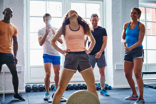 Woman stretching after lifting weights with friends in the backg