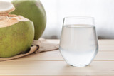 a glass of coconut water on wooden table