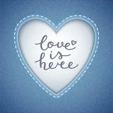 love is here lettering, vector handwritten text on denim texture