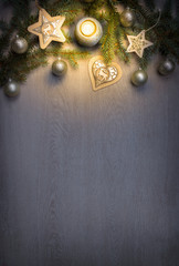 Christmas fir tree with decoration and candle on wooden board