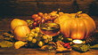 pumpkins, grapes and grape juice, apples. on a wooden surface. a burning candle. wide