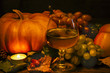 a glass of grape juice, pumpkins, grapes, apples. on a wooden surface. against a dark background