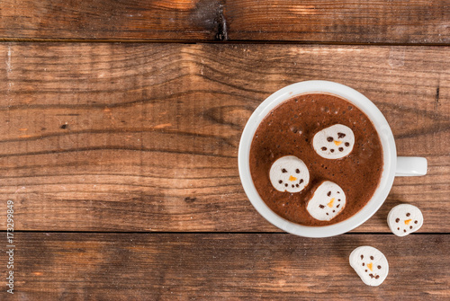 Papiers peints Chocolat Traditional Christmas drink idea. Hot chocolate mug with marshmallow, decorated in the form of snowmen, On wooden table top view copy space
