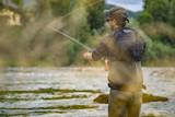 Angler mit Wathose und Fliegenrute im Wasser beim Angeln bei Sonne im klaren Fluss stehend und werfend - 173300294