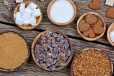 Various kinds of sugar in a bowls on wooden table