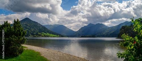Fotobehang Bergen Sandiges Ufer eines Bergsees im Hintergrund die Berge in den Wolken.