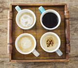 Different cups of coffee on wooden table - 173395644