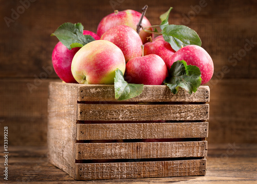 fresh red apples leaves with in a wooden box