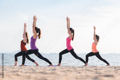 Plakat Yoga class at sea beach in evening ,Group of people doing Warrior poses with clam relax emotion at beach,Meditation pose,Wellness and Healthy balance lifestyle.