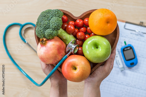 Foto Murales Diabetes monitor, Cholesterol diet and healthy food eating nutritional concept with clean fruits in nutritionist's heart dish and patient's  blood sugar control record with diabetic measuring tool kit