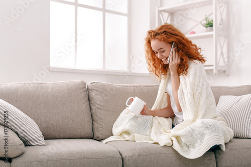 Cozy home. Girl in a blanket with mobile Poster