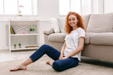 Young redhead woman sitting on the floor - 173429489