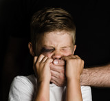 Scared young boy with an adult man's hand covering his mouth - 173437841