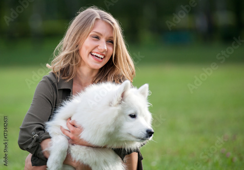 Pretty happy girl playing with her dog at the park, samoyed