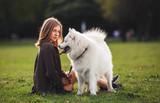 Pretty girl and samoyed dog on grass