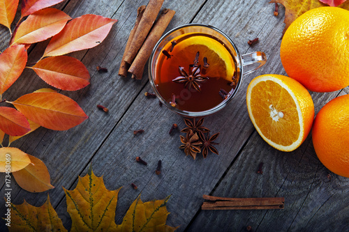 hot tea with spices and orange amid autumn leaves